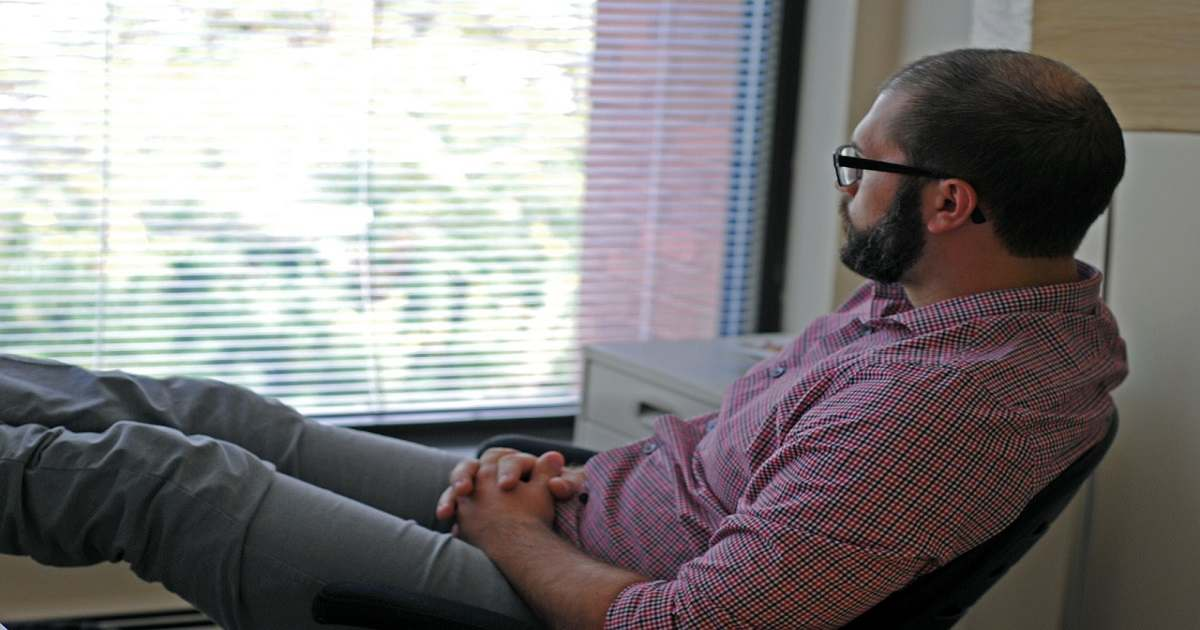 A man sitting at the office desk and looking outside - Common Financial Mistakes