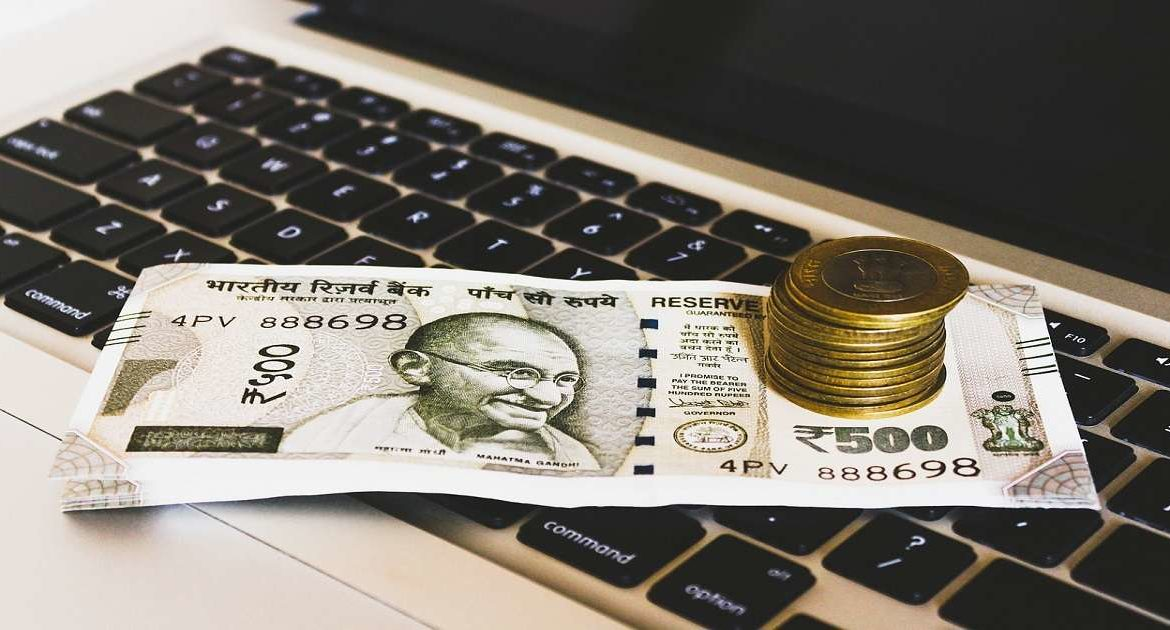 This Image show some India notes coin and a laptop - Ways to make money at home